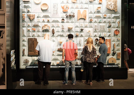 Visitors examine a display case of Roman artifacts found during the restoration of the Temple of Mithras, London Mithraeum, City of London - Stock Photo