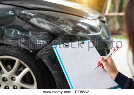 Filling Insurance Form Near Damaged and examining Car, Traffic Accident and insurance concept. - Stock Photo