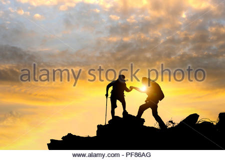 Male and female hikers climbing up mountain cliff and one of them giving helping hand. People helping and, team work concept. - Stock Photo