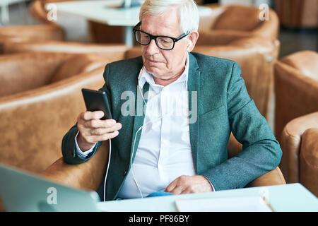 Contemporary Senior Man Using Smartphone in Cafe - Stock Photo