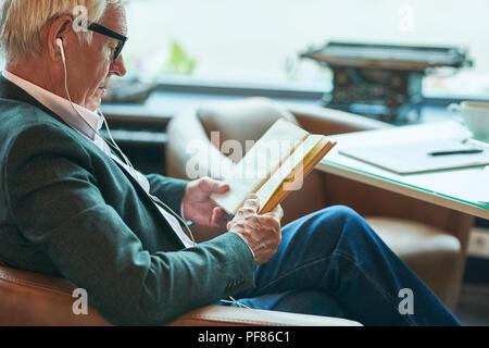 Contemporary Senior Man Reading in Cafe - Stock Photo