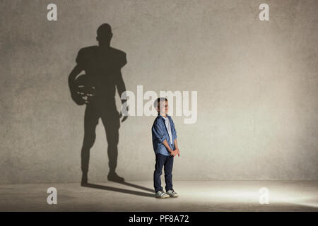 American Football champion. Childhood and dream concept. Conceptual image with boy and shadow of fit athlete on the studio wall - Stock Photo