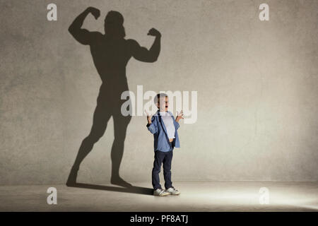 The little boy dreaming about athletic bodybuilder figure with muscles. Childhood and dream concept. Conceptual image with boy and shadow of fit athlete on the studio wall - Stock Photo