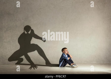 The little boy dreaming about hero figure with muscles. Childhood and dream concept. Conceptual image with boy and shadow of fit athlete on the studio wall - Stock Photo