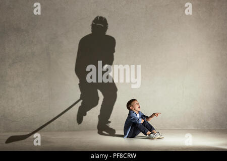 Ice hockey champion. Childhood and dream concept. Conceptual image with boy and shadow of fit athlete on the studio wall - Stock Photo