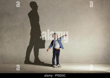 The little boy dreaming about businessman or diplomat profession. Childhood and dream concept. Conceptual image with boy and shadow of man in suit on the studio wall - Stock Photo
