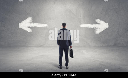 Businessman in front of a choice arrows and thinking about it. - Stock Photo