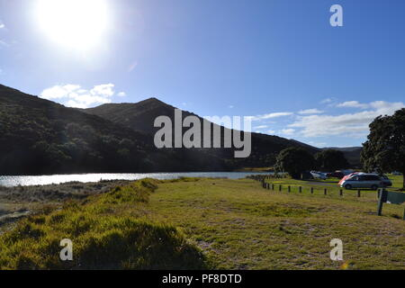 New zealand camping next to a river with parking on the grass - Stock Photo