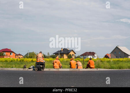 Four workers resting on the road construction site with a houses behind them - Stock Photo
