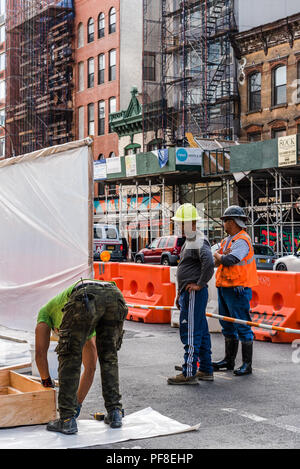 New York City, USA - June 20, 2018: Three workers working on construction site in street in New York City - Stock Photo