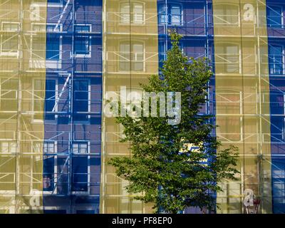 Close up of the facade of a building covered of a scaffolding and a transparent plastic - Stock Photo