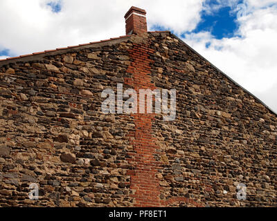 Stone gable of a house with exposed brick chimney. Close up - Stock Photo