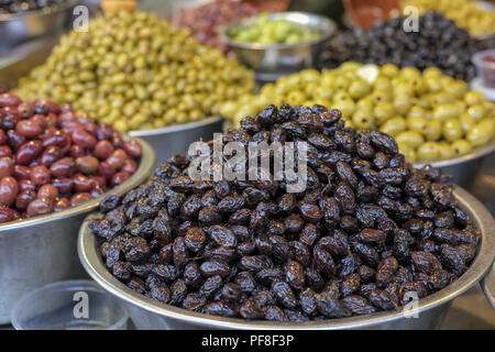 Olives of different types and colours in a market stall Photographed in Tel Aviv, Israel - Stock Photo