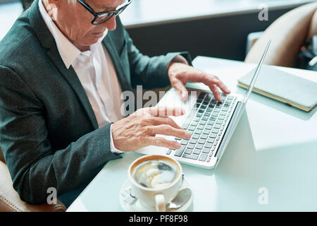 Elderly businessman using laptop in cafe - Stock Photo