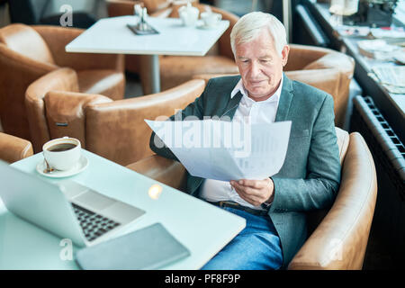 Aged businessman reading documents in cafe - Stock Photo
