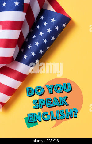 some flags of the United States and the question do you speak English? on a yellow background - Stock Photo