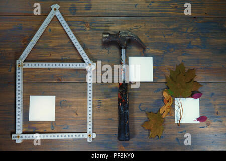Conceptual construction and renovation still life with a flat lay design of a house formed by a ruler, hammer and autumn leaves with blank sticky note - Stock Photo