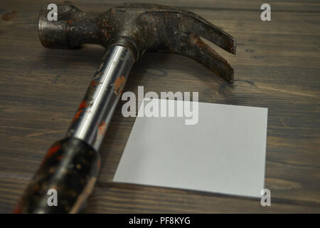 Conceptual construction and renovation still life with a hammer and blank sticky note on a rustic wood background - Stock Photo