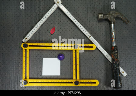 Conceptual construction and renovation still life with a flat lay design of a house formed by a yellow and white rulers, hammer and autumn leaves with - Stock Photo