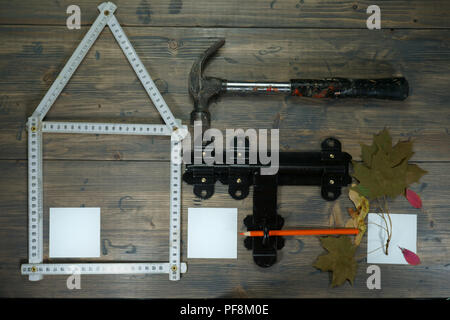 Conceptual construction and renovation still life with a flat lay design of a house formed by a ruler, hammer, old metal hasp and staple lock and autu - Stock Photo