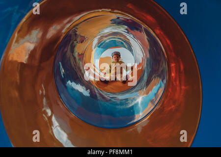Kid climbing and sliding on outdoor playground in the park.Child on colorful slide. - Stock Photo