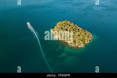Drone shot of beautiful small island surrounded by crystal clear blue sea water and fast motorboat running away leaves a white trail in the waves of t - Stock Photo