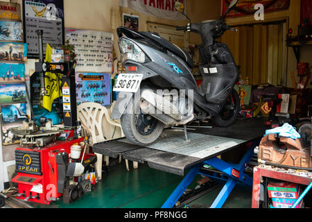 20 February 2018, Tainan Taiwan: scooter on a scissor lifting platform in a workshop for scooters in Tainan Taiwan - Stock Photo