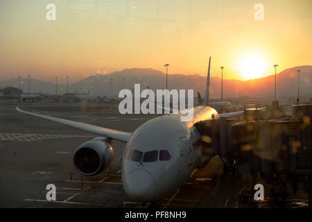 Airplane parking at Hong Kong International airport in sunrise - Stock Photo