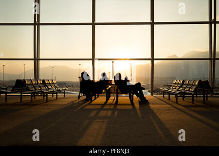 Passenger sitting in a lobby airport waiting for flight - Stock Photo