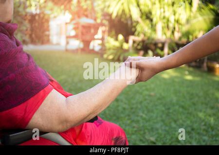 Caretaker pushing senior woman in wheel chair  - Stock Photo