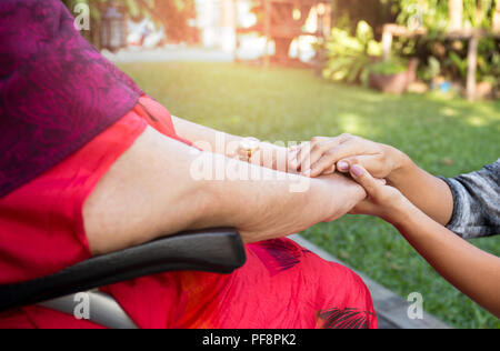 Caretaker pushing senior woman in wheel chair  - Stock Photo