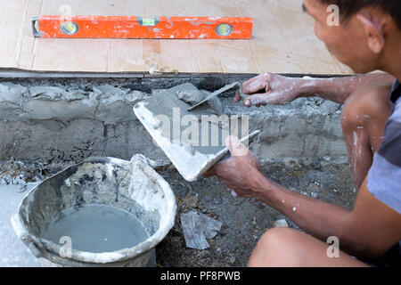 Construction hand holding trowel plastering concrete  - Stock Photo