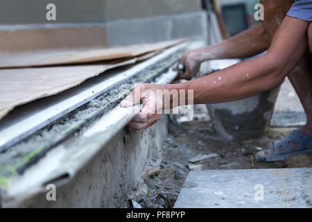 Man shape the edge of the floor with plasterer concrete cement  - Stock Photo