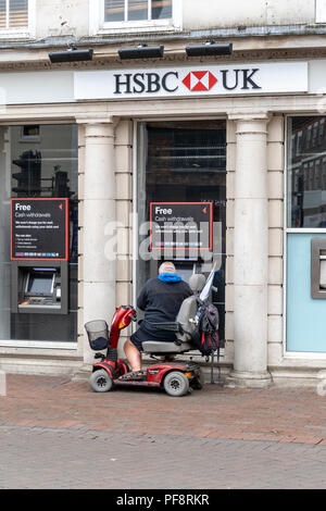 Man on mobility scooter using an ATM cash machine outside of a UK bank - Stock Photo