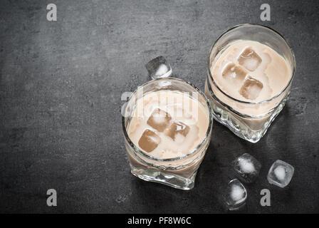 Irish cream liqueur in glasses with ice on black. - Stock Photo