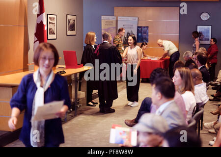 New Canadian citizens receiving their Citizenship certificates at a Citizenship ceremony in Vancouver, British Columbia, Canada 2018 - Stock Photo