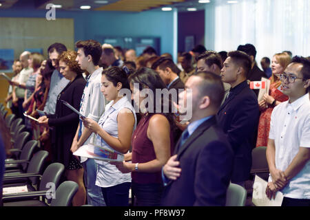 People singing Canadian national anthem, O-Canada, at a Citizenship ceremony in Vancouver, British Columbia, Canada 2018 - Stock Photo