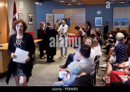 New Canadian citizens receiving their Citizenship certificates from the judge in a Citizenship ceremony venue in Vancouver, British Columbia, Canada 2 - Stock Photo