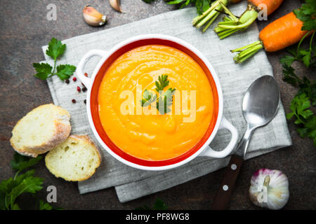 Carrot pumpkin cream-soup on dark stone table. Vegetarian vegetables soup. Top view. - Stock Photo