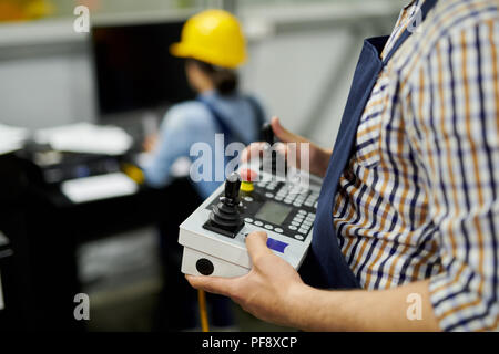 Mid section shot of unrecognizable  factory worker operating machine unit pressing buttons on control panel, copy space - Stock Photo
