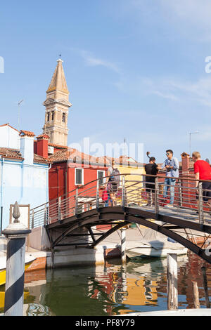 Sunset in the colourful fishing village on Burano Island, Venice, Veneto, Italy, Tourists on bridge taking selfies, reflections canal, leaning bell to - Stock Photo