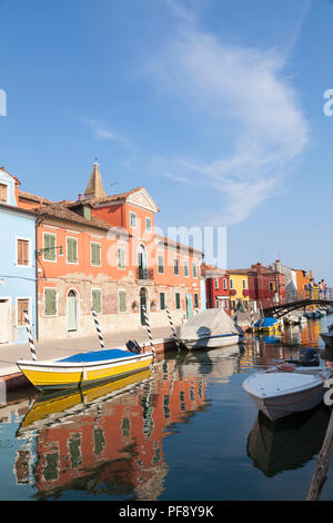 Sunset in the colourful fishing village on Burano Island, Venice, Veneto, Italy with tourists on bridge over canal with reflections and boats - Stock Photo