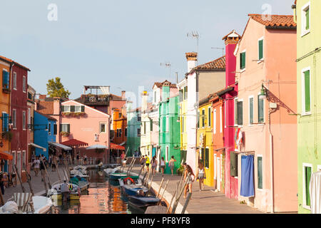 Sunset in the colourful fishing village on Burano Island, Venice, Veneto, Italy. Canal with boats, reflections, tourists - Stock Photo