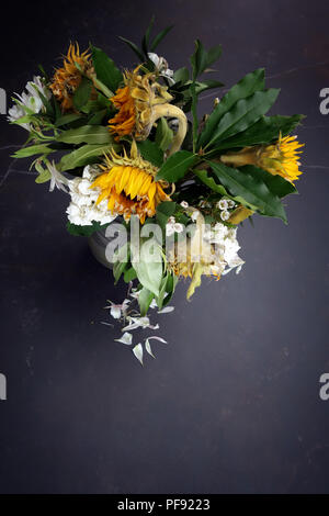 Looking slightly down at a vase of dying flower arrangement, large once bright now dying sun flowers in a vase on a very large marble dining table - Stock Photo