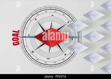 Concept vision leadership goal and workforce leader management with red paper ship on compass needle pointing the red word goal leading among paper sh - Stock Photo