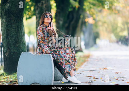 Young woman in sunglasses with milkshake. Outdoor lifestyle portrait of pretty smiling female with little puppy in autumn park - Stock Photo