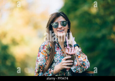 Young woman in sunglasses with milkshake. Outdoor autumn lifestyle portrait of pretty smiling female. - Stock Photo