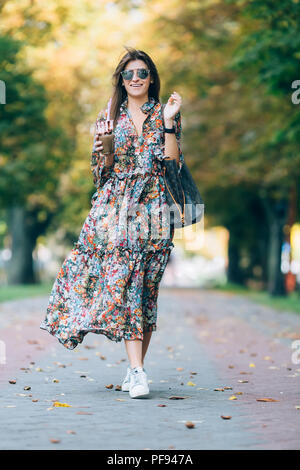 Young woman in sunglasses with milkshake. Outdoor lifestyle portrait of pretty smiling female walking in autumn park - Stock Photo
