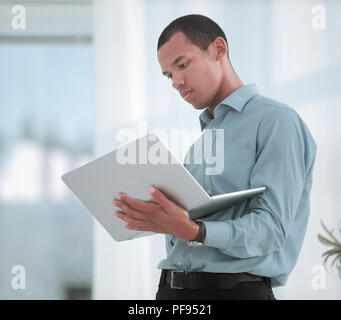 serious Manager working on a laptop standing in office - Stock Photo