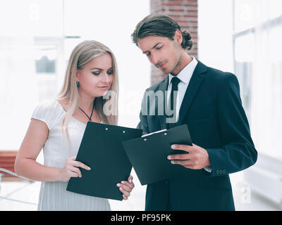 businessman and businesswoman discussing documents before the me - Stock Photo